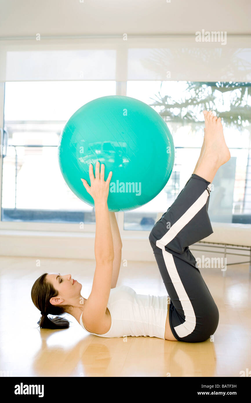 Woman using exercise ball for exercising because their inherent instability causes more of the body and muscles - Stock Image