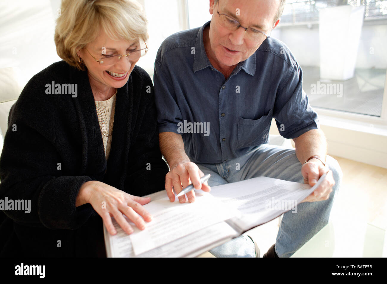 Couple signing forms. - Stock Image