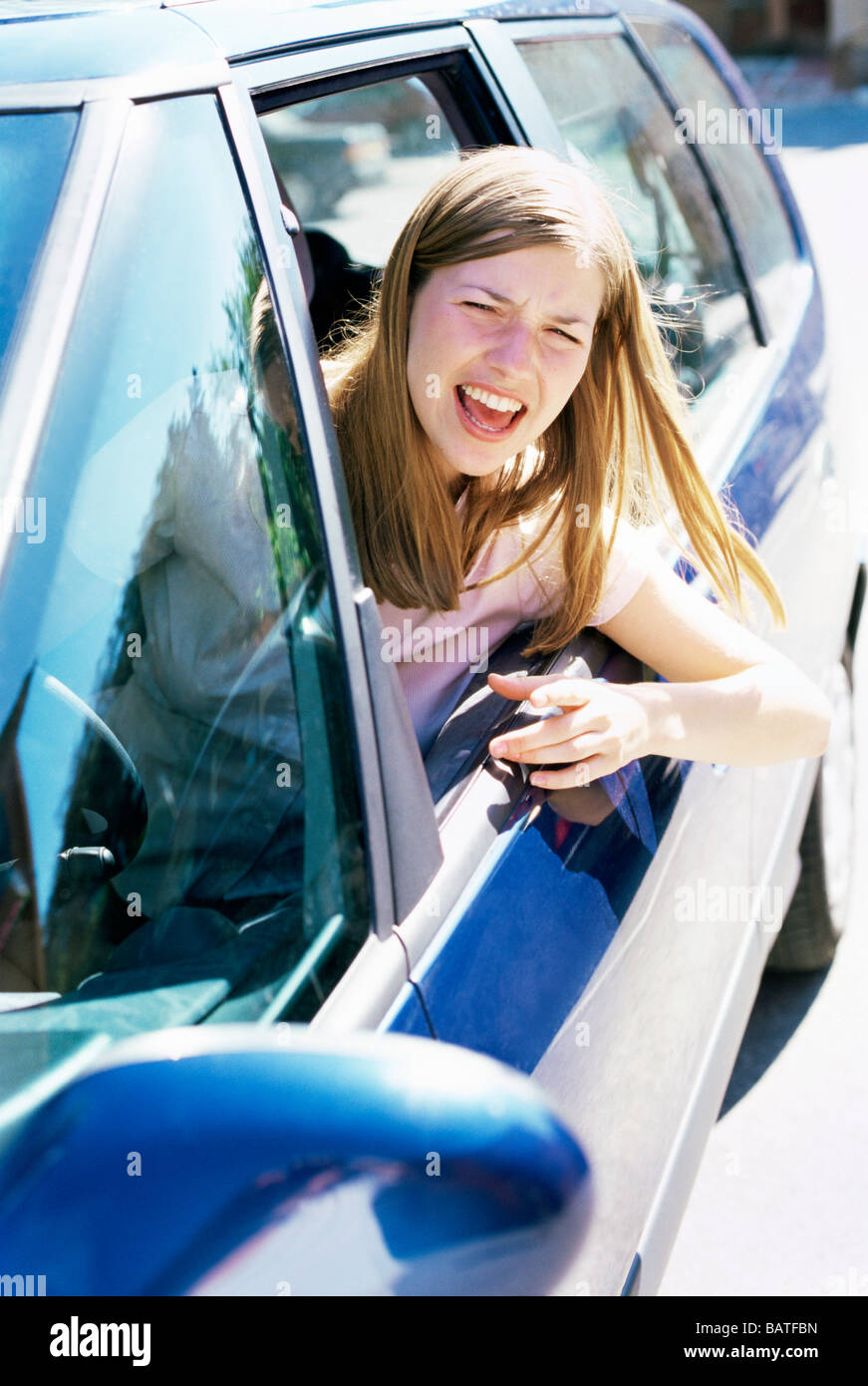 Road rage. Young woman shoutingout of a car window. Stock Photo
