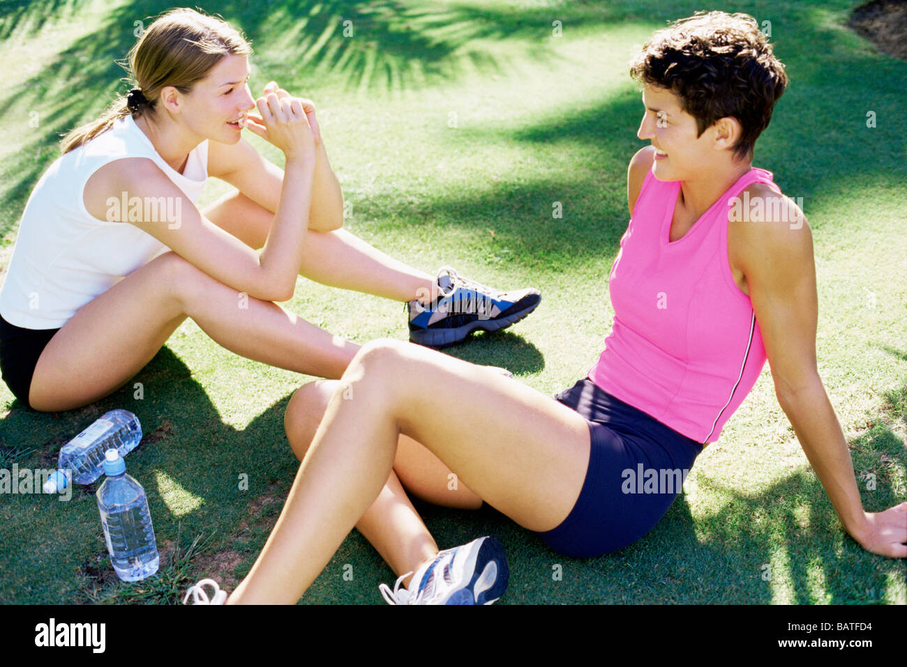 Friendship. Two women relaxing onthe grass. - Stock Image