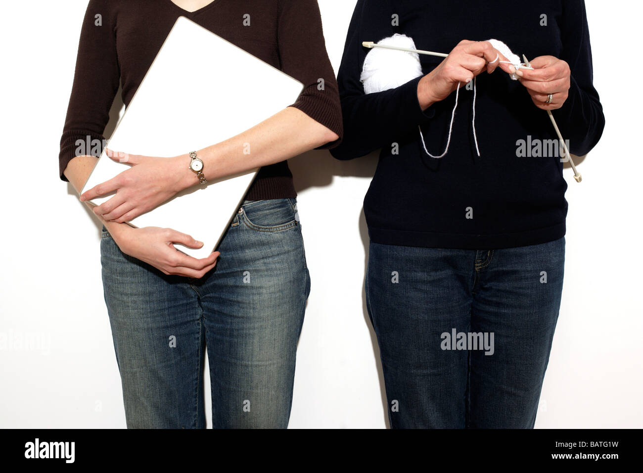Leisure activities. The woman on the right is knitting and the woman on the left is carrying a laptop. - Stock Image