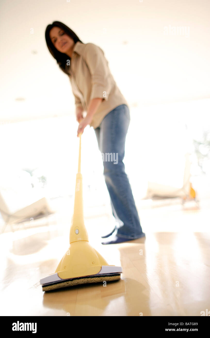 Woman mopping a floor. - Stock Image