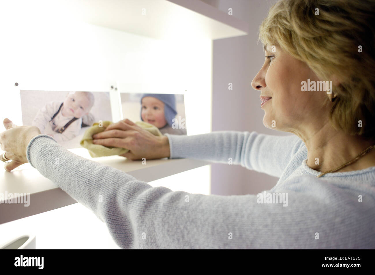 Woman dusting family photographs. - Stock Image