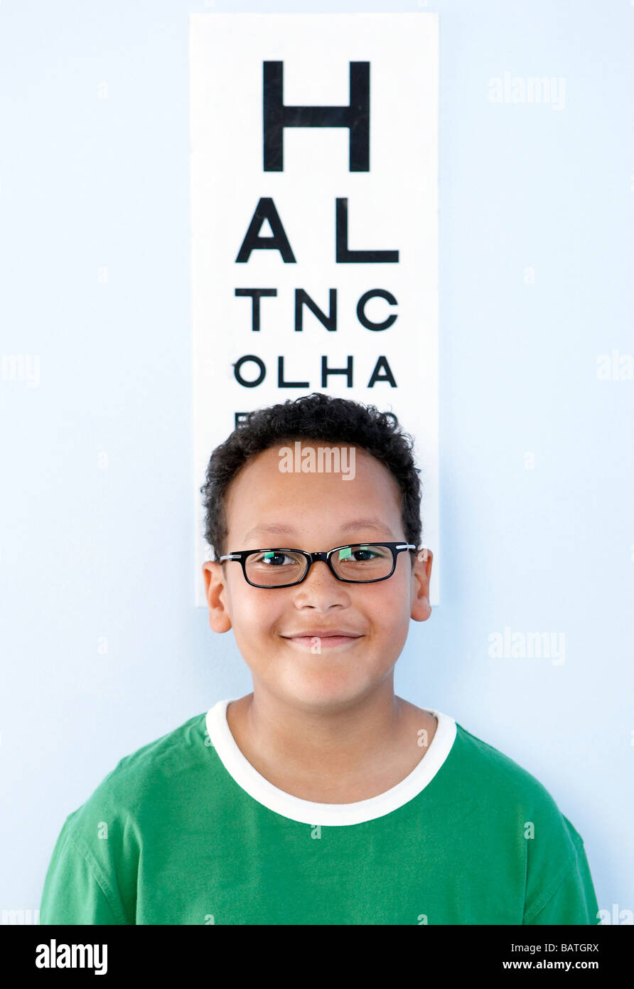 Eye examination. Boy wearing glasses standing under an eye chart. - Stock Image
