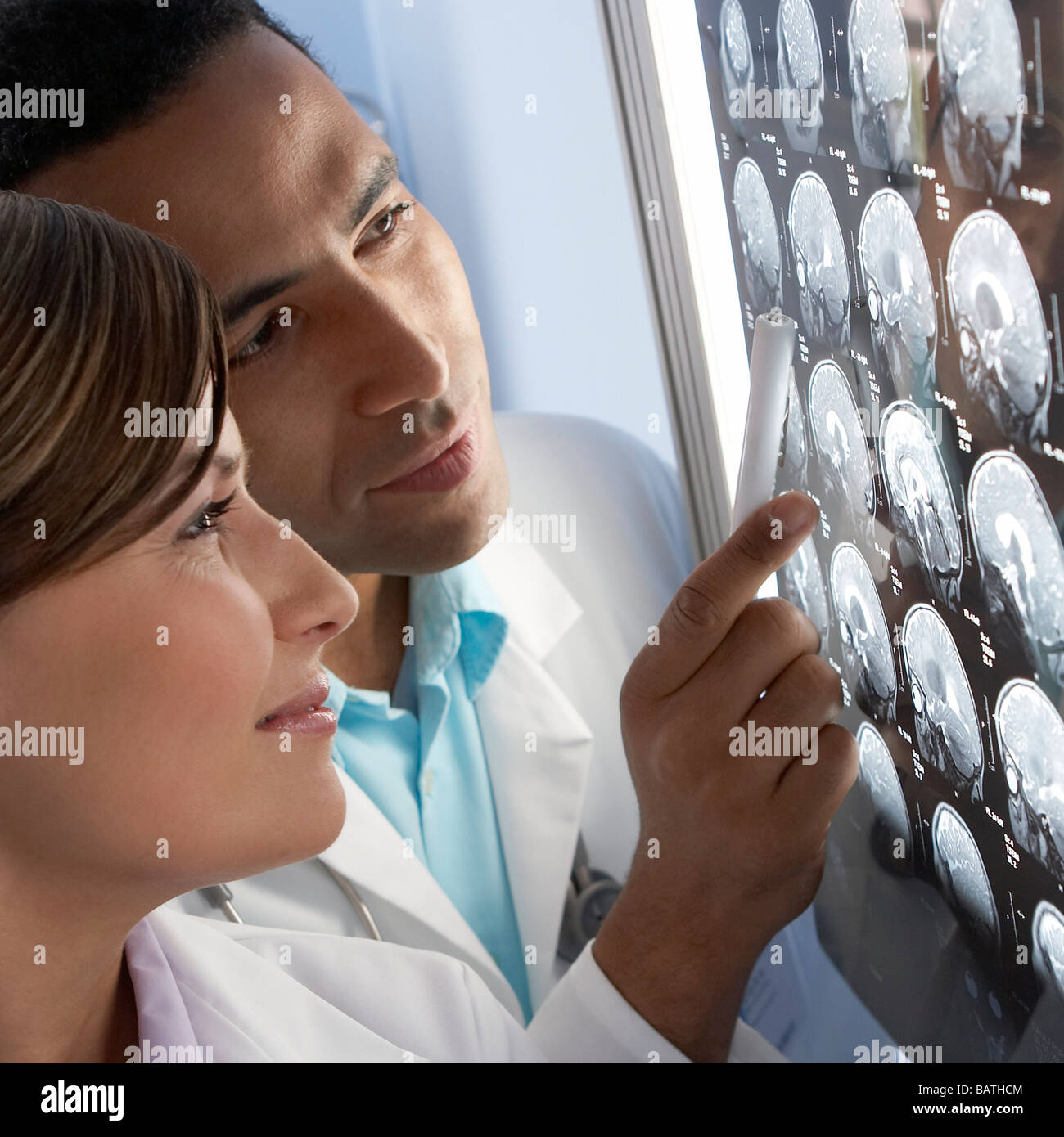 Doctors examining MRI scans.The scans are sagittal (side view) sections through a patient head - Stock Image
