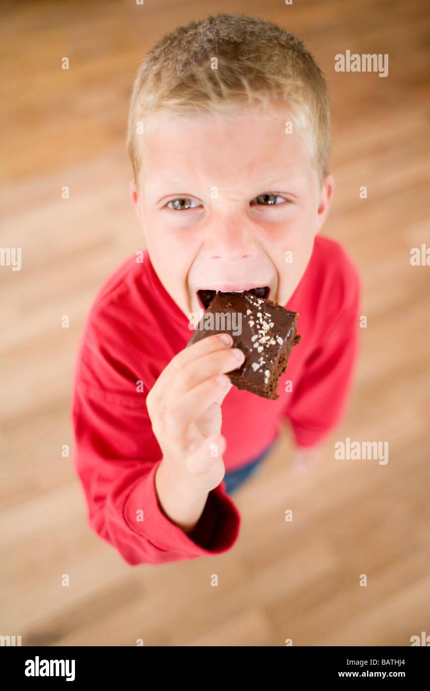 Boy eating chocolate cake. - Stock Image