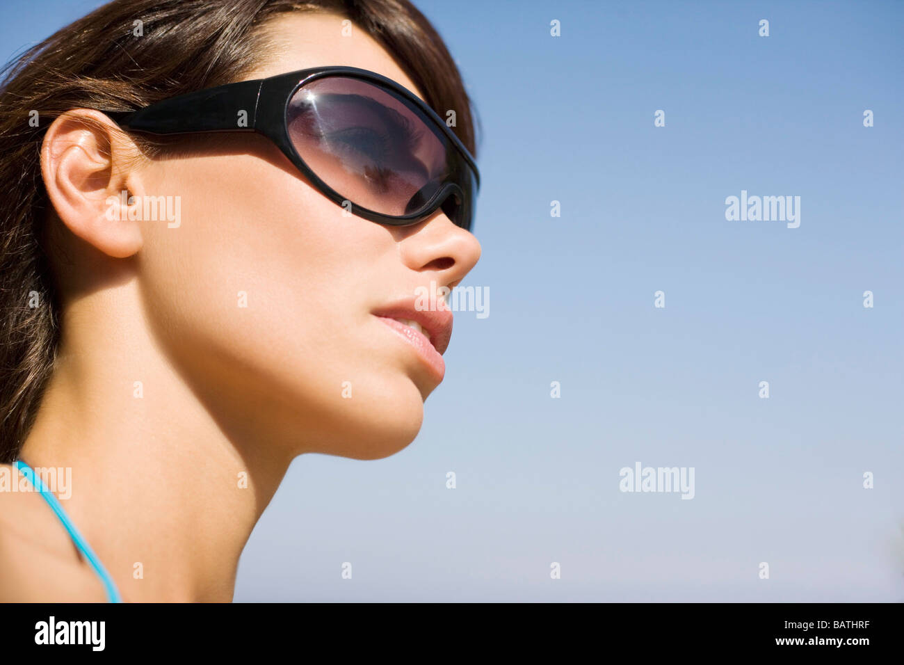 Woman wearing sunglasses. The lenses protect the eyes from the UV radiation insunlight. - Stock Image