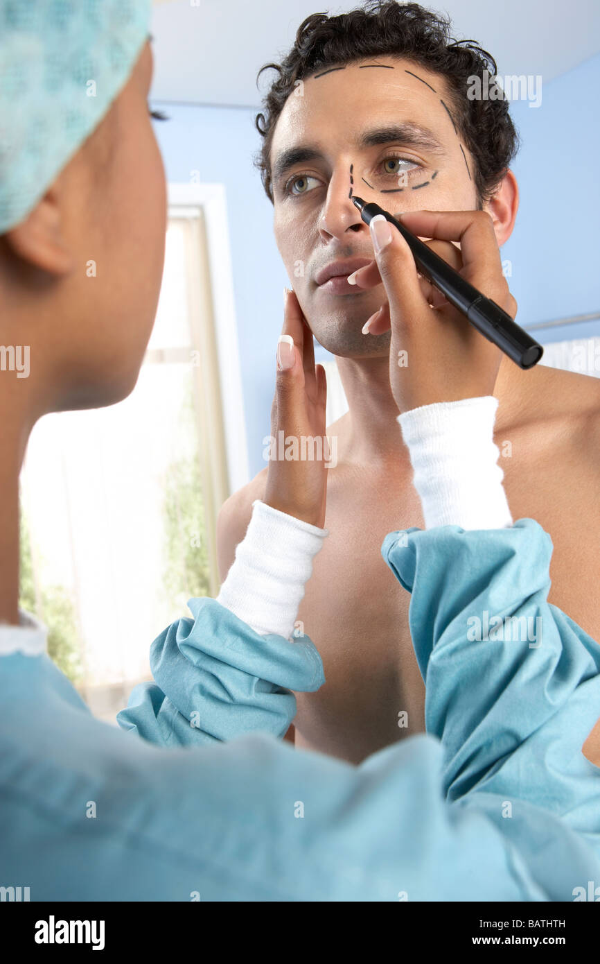 Cosmetic surgery. Surgeon drawing marks on a patient face in preparation for cosmetic surgery - Stock Image