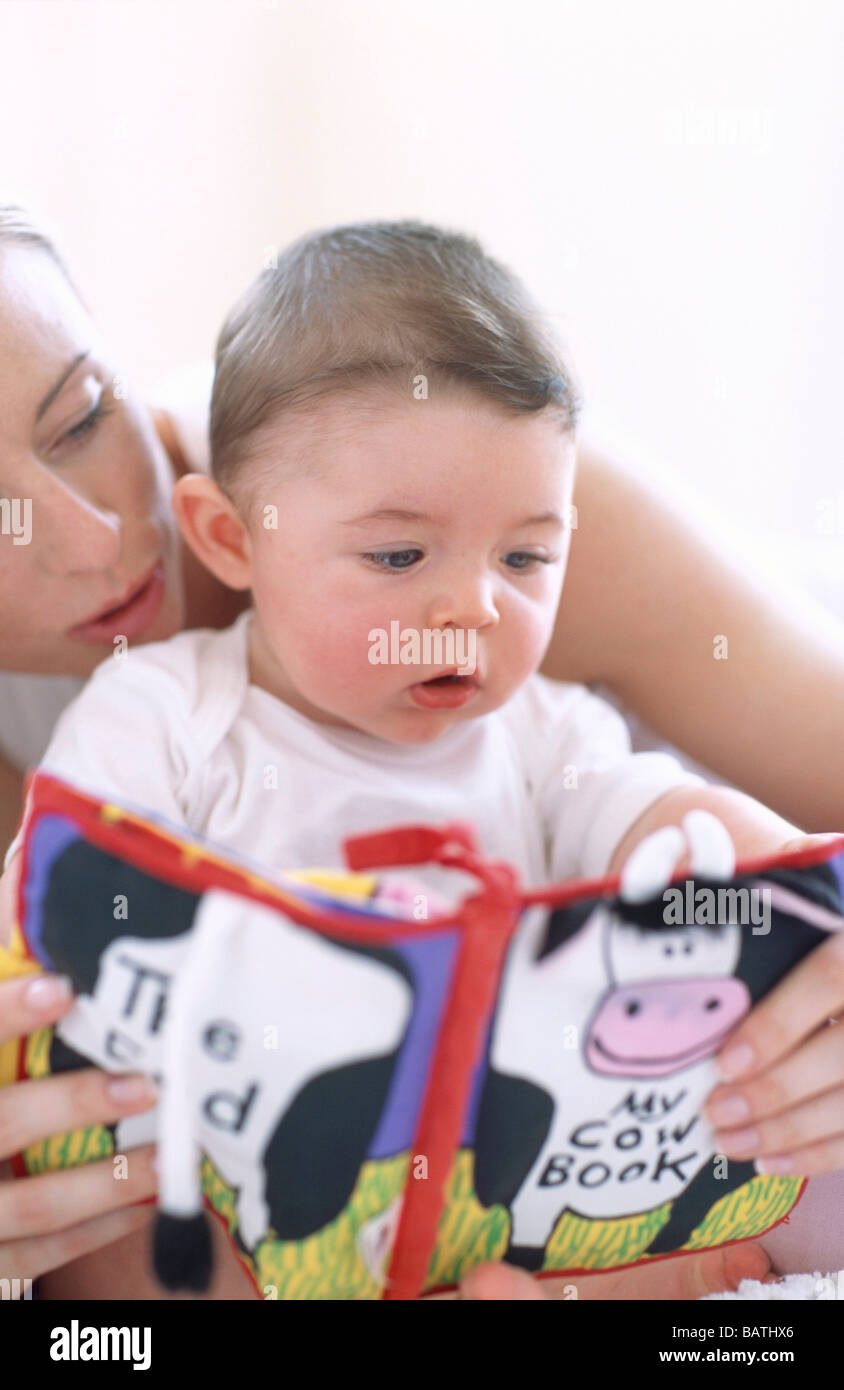 Mother reading to baby boy.Faces of a mother reading aloud to her 6-month-oldbaby boy. - Stock Image