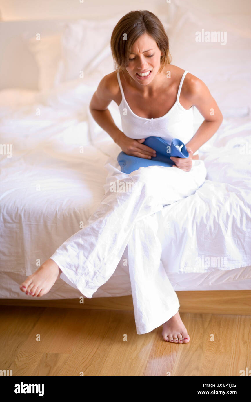 Menstrual pain. Womanholding a hot water bottle against her abdomen toalleviate menstrual cramps. - Stock Image