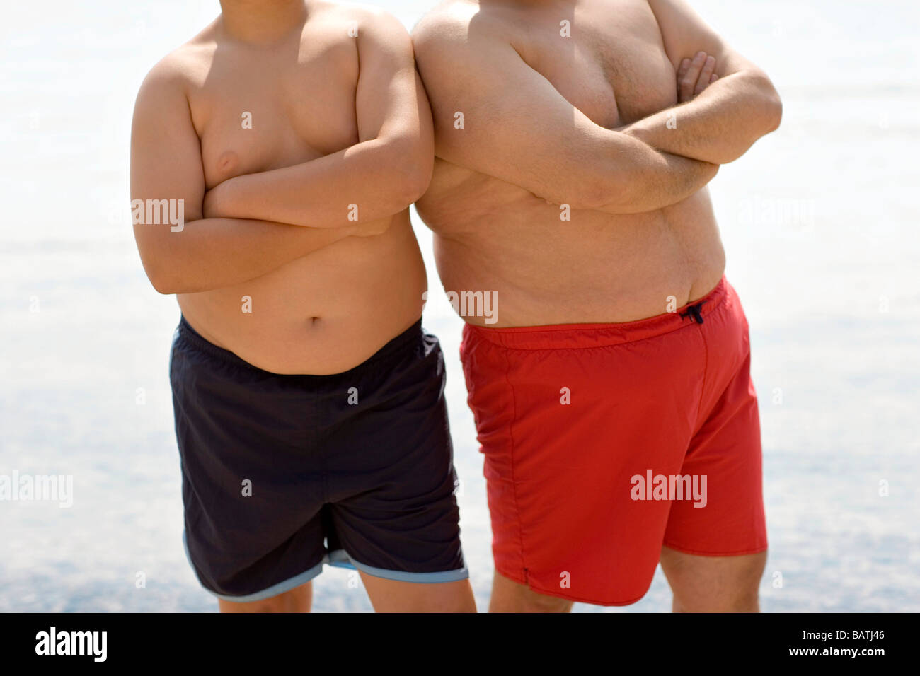 Overweight boy and man with their arms folded. - Stock Image