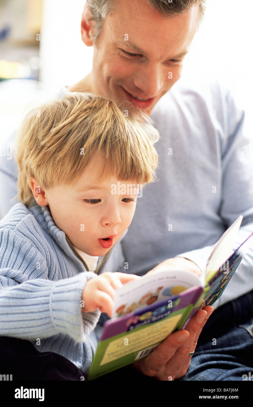 Fatherhood. Excited three year old reading a book with his father. - Stock Image