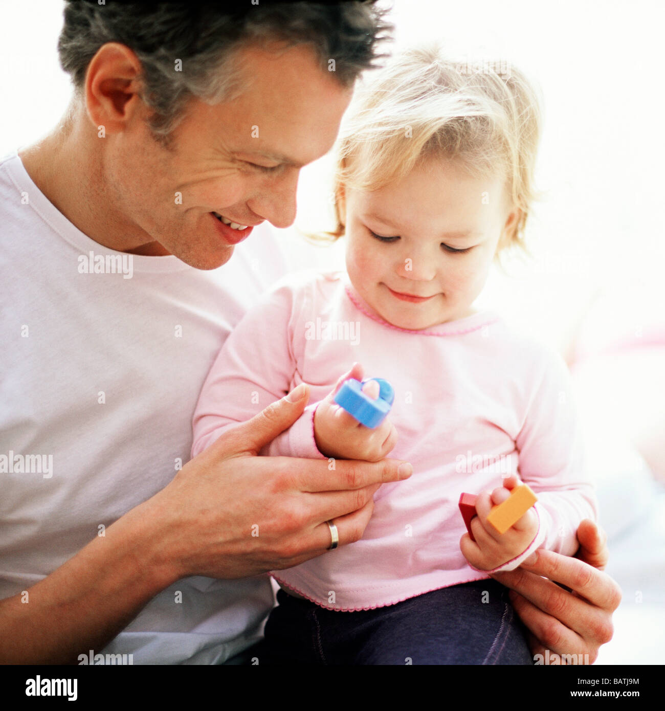 Fatherhood. Father playing with his one year old daughter while holding her on his lap. - Stock Image