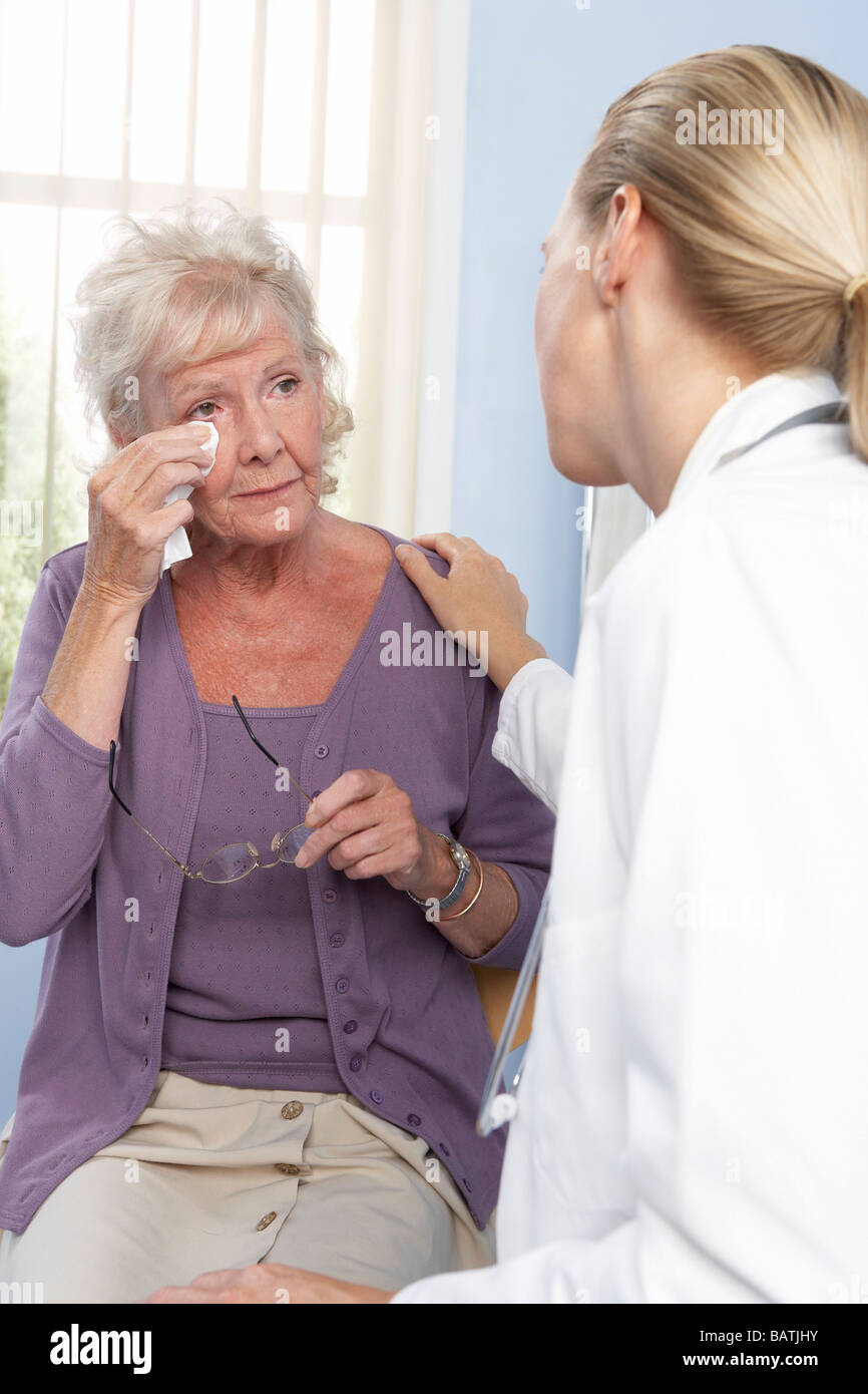 Breaking bad news. General practitioner breaking bad news to an elderly patient. - Stock Image