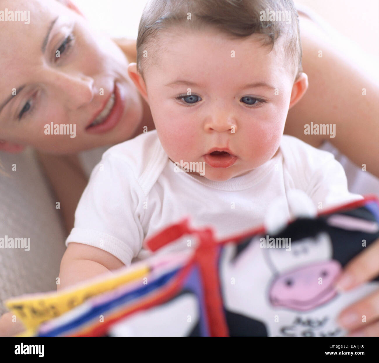 Mother reading to baby boy.Faces of a mother and her 6 monthsold baby boy as she reads aloud to him. - Stock Image
