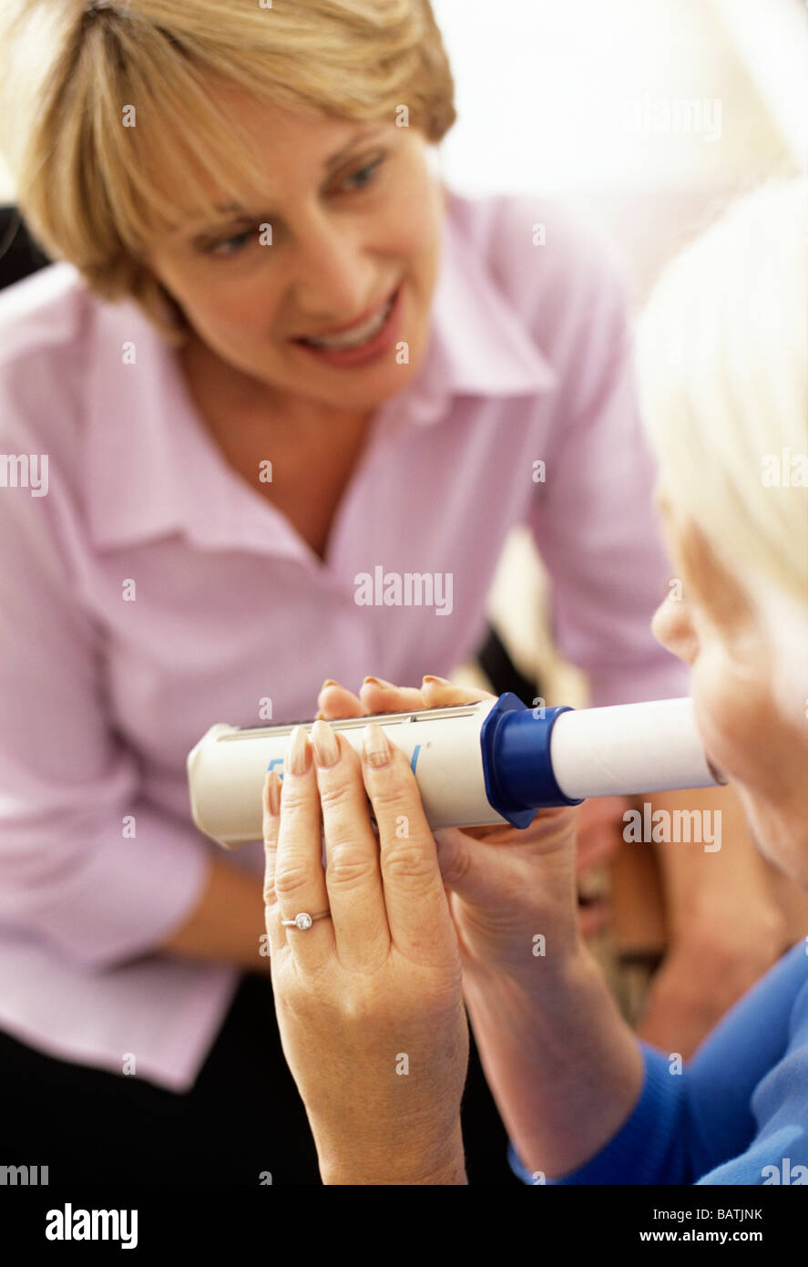 Lung function test. 63-year-old woman breathing into a peak flow meter (spirometer). - Stock Image