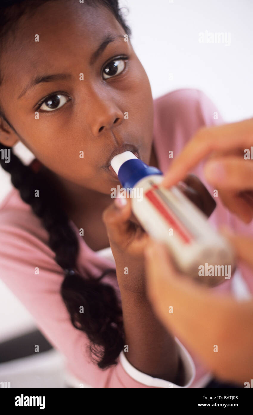 Lung function test. Nine year old girl breathing into a peak flow meter (spirometer). - Stock Image