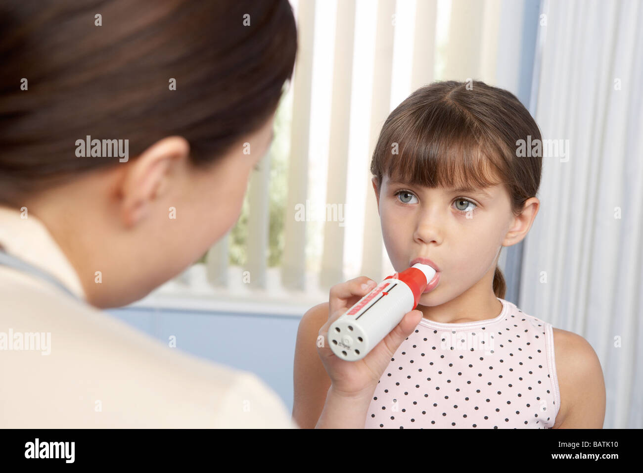 Lung fucntion test. Six year old girl breathing into a peak flow meter (spirometer). - Stock Image