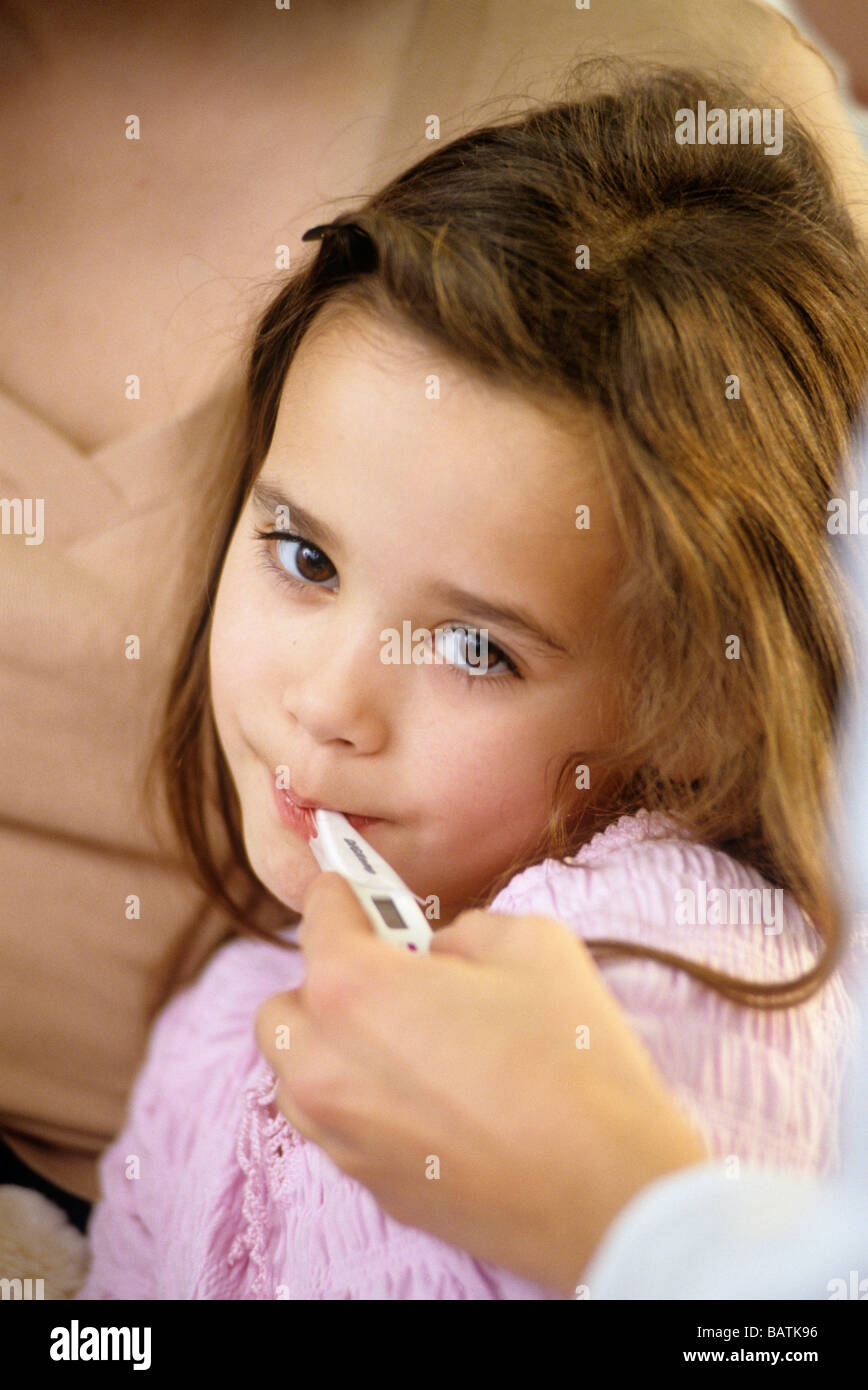 Temperature reading. Young girl having her temperature taken by a doctor. Stock Photo