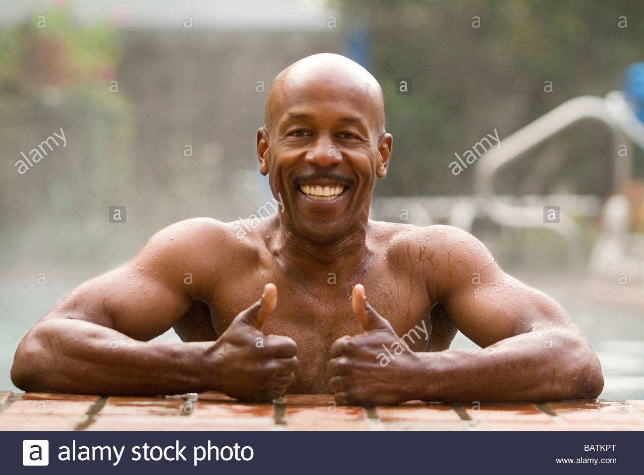 African Man In Pool Giving Thumbs Up Gesture