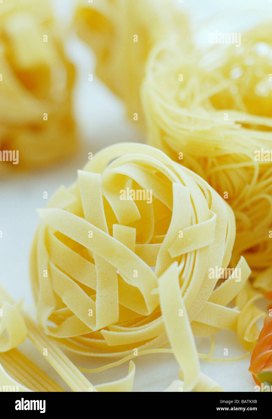Dried pasta ribbons. Pasta is a flour-based food product, and so it contains lots ofcarbohydrates from the cereal - Stock Image
