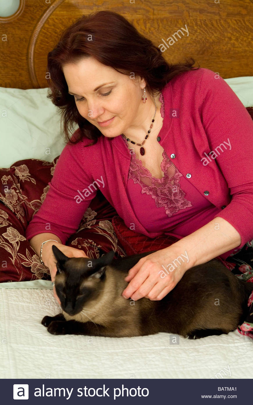 Woman petting cat on bed - Stock Image