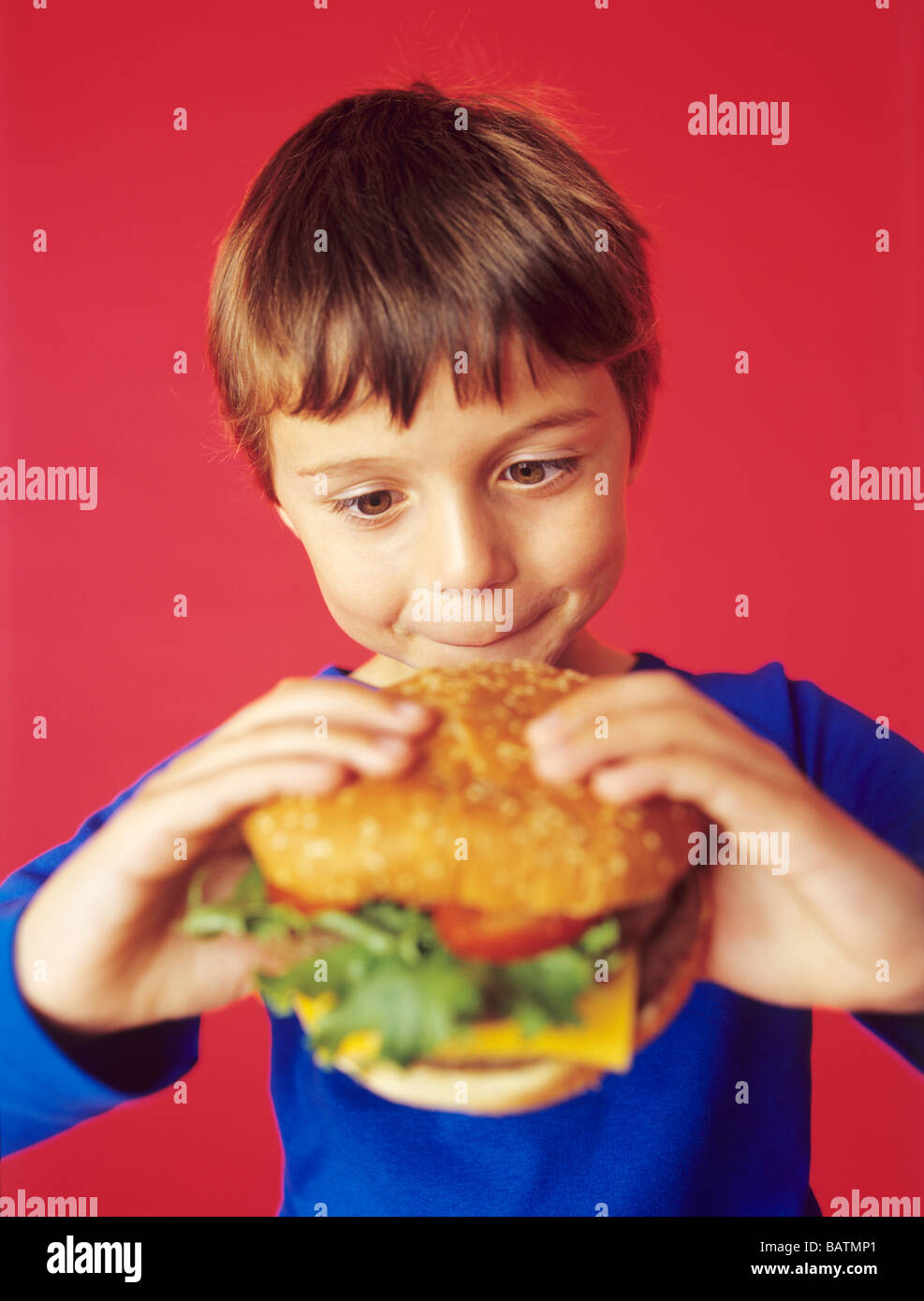 Fast food. 7-year-old boyeating a burger with cheese. If eaten in excess,such food can lead to obesity and heart - Stock Image