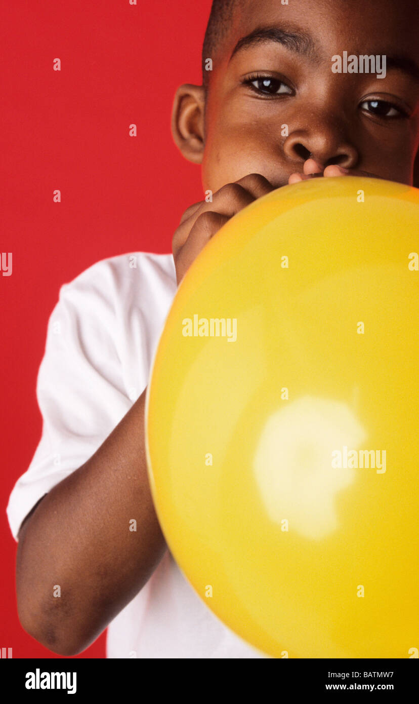 Blowing up a balloon. 6-year-old boy blowing up a yellow balloon. - Stock Image