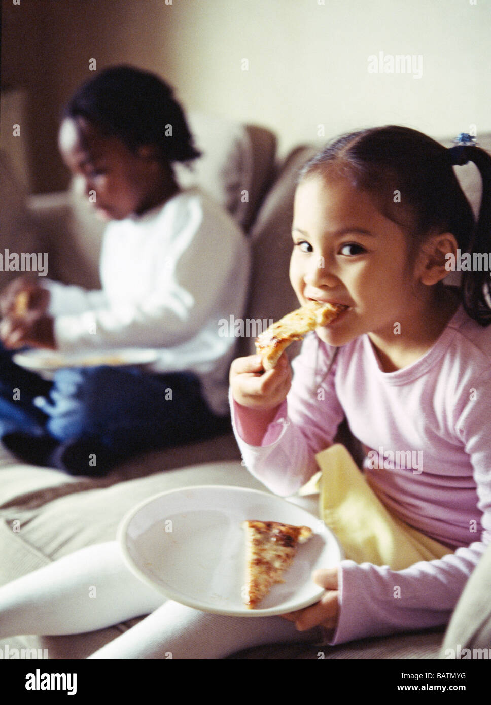 Junk food. Five-year-old girl taking a bite from a slice of pizza. In the background, a five-year-old boy is also - Stock Image