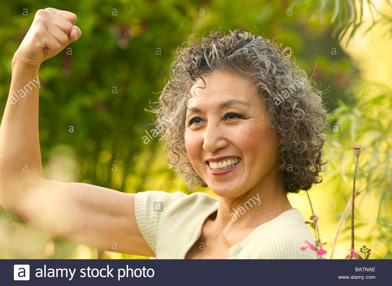 Asian woman flexing biceps in garden - Stock Image