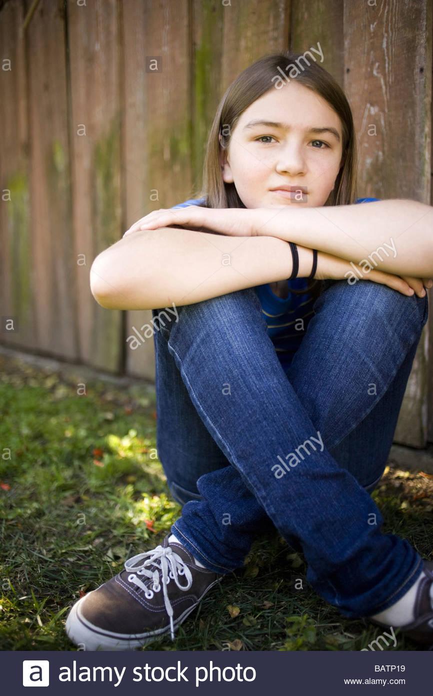 Girl sitting in backyard - Stock Image