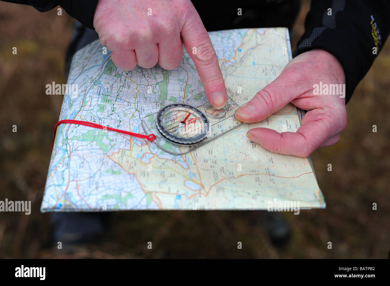 A mans hands holding a map and compass for orienteering and