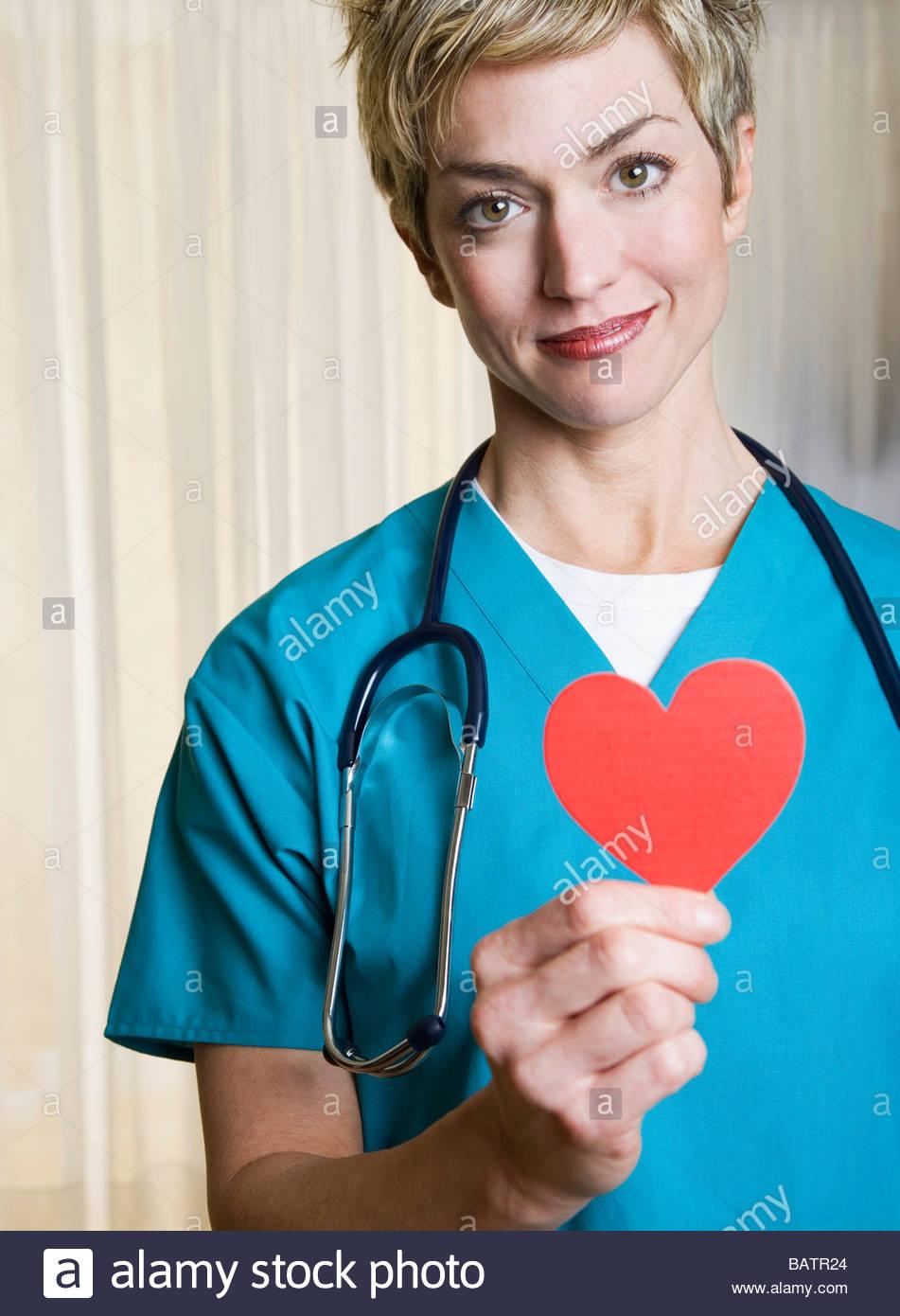 Female nurse holding heart-shaped cut out - Stock Image