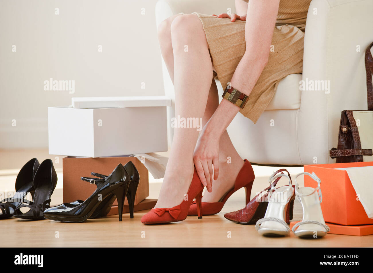 Woman trying on high heel shoes in shop - Stock Image