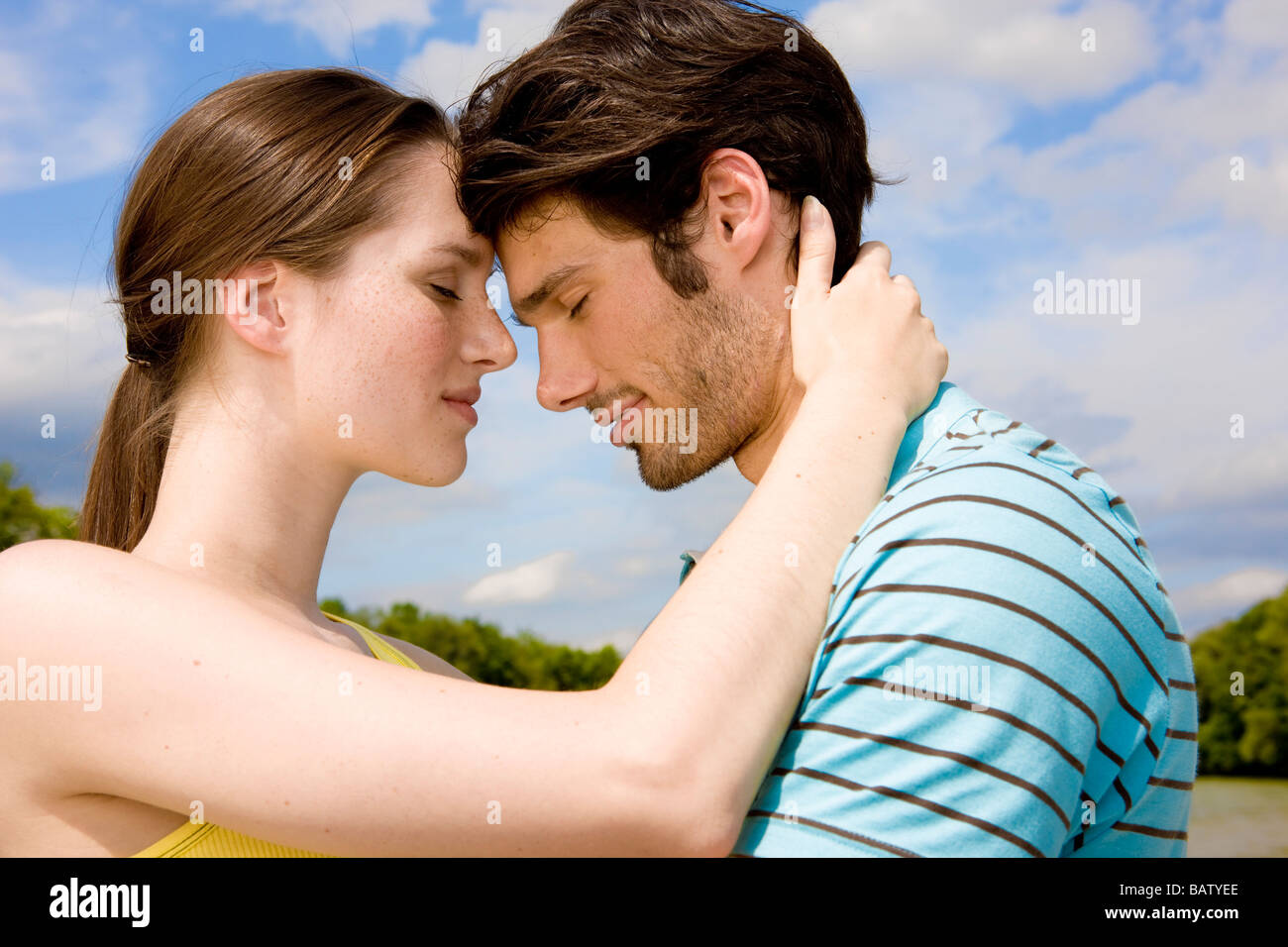 portrait of young couple in tender embrace outdoors - Stock Image