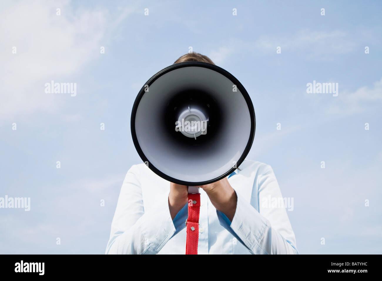 portrait of young businesswoman hidden behind megaphone - Stock Image