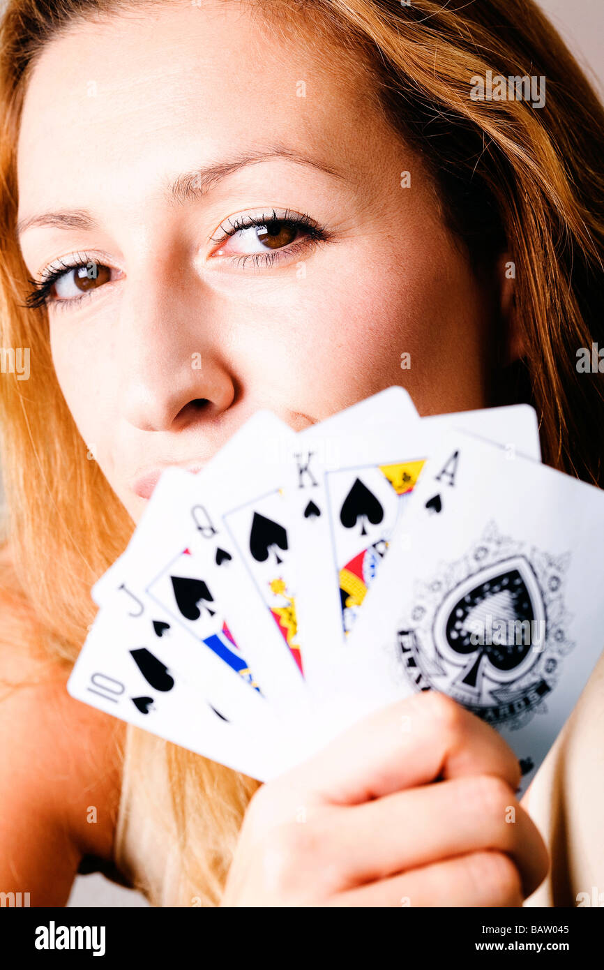 headshot of young woman holding playing cards - Stock Image