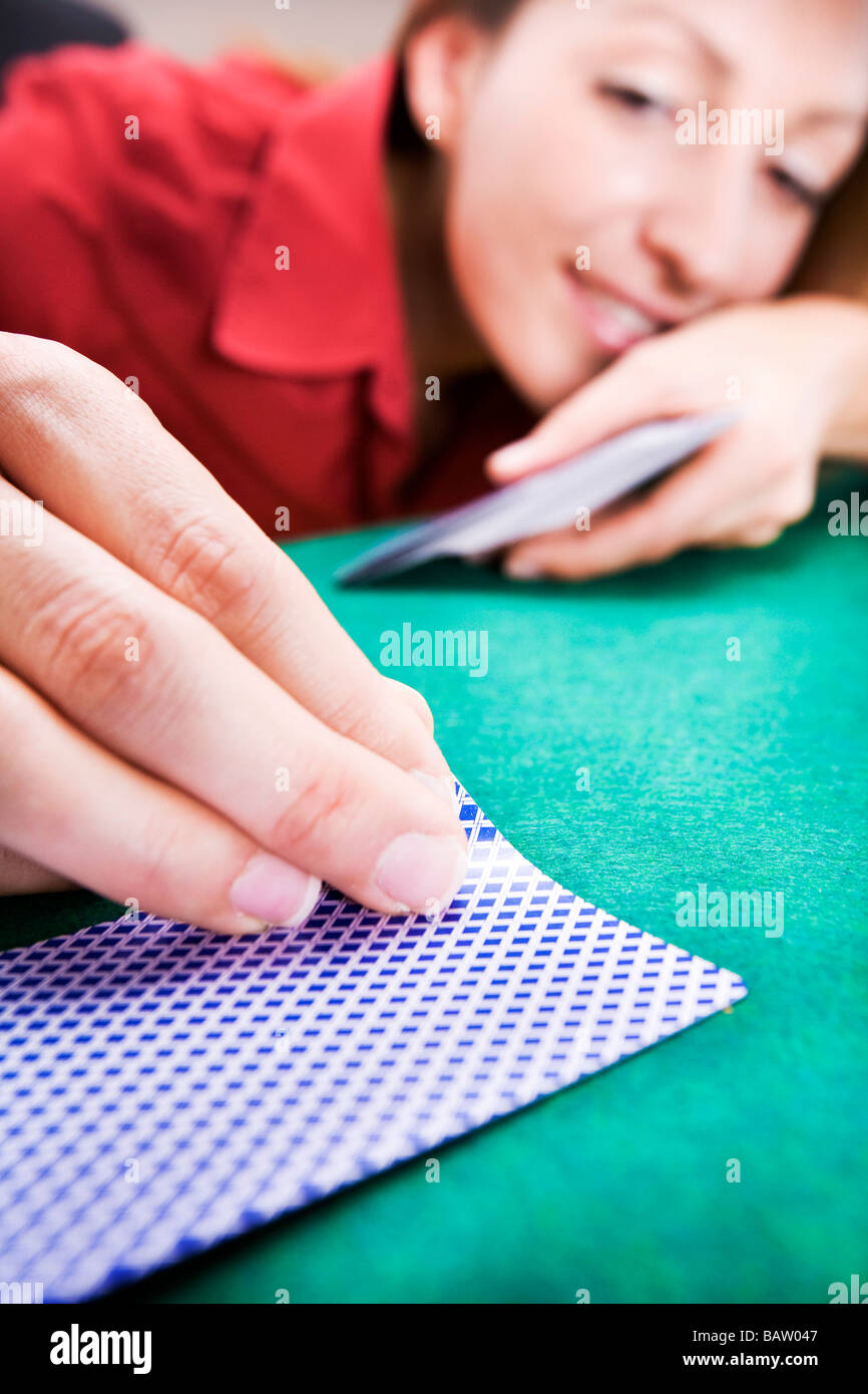 young woman peeping at playing card - Stock Image