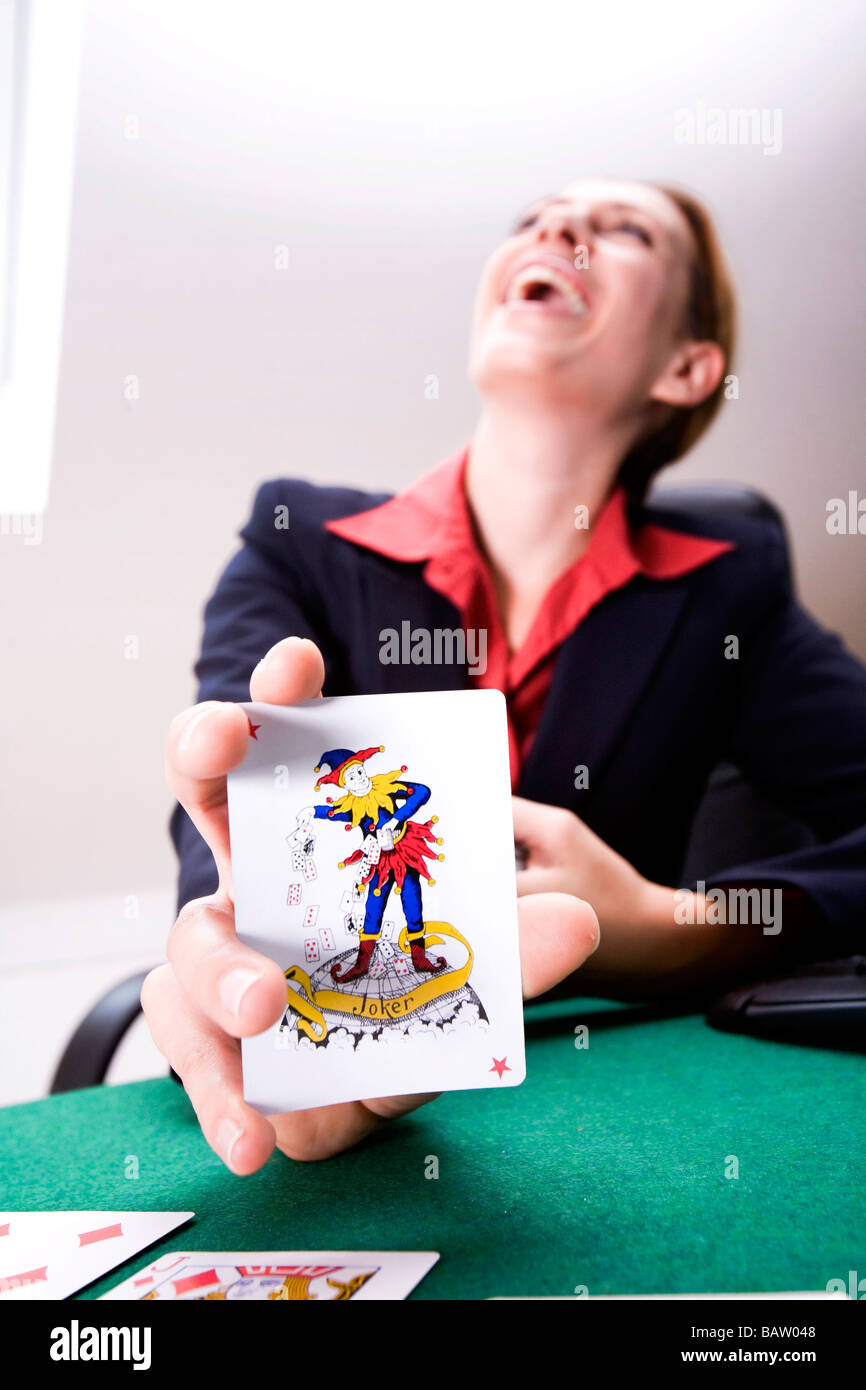 happy young woman holding joker card - Stock Image