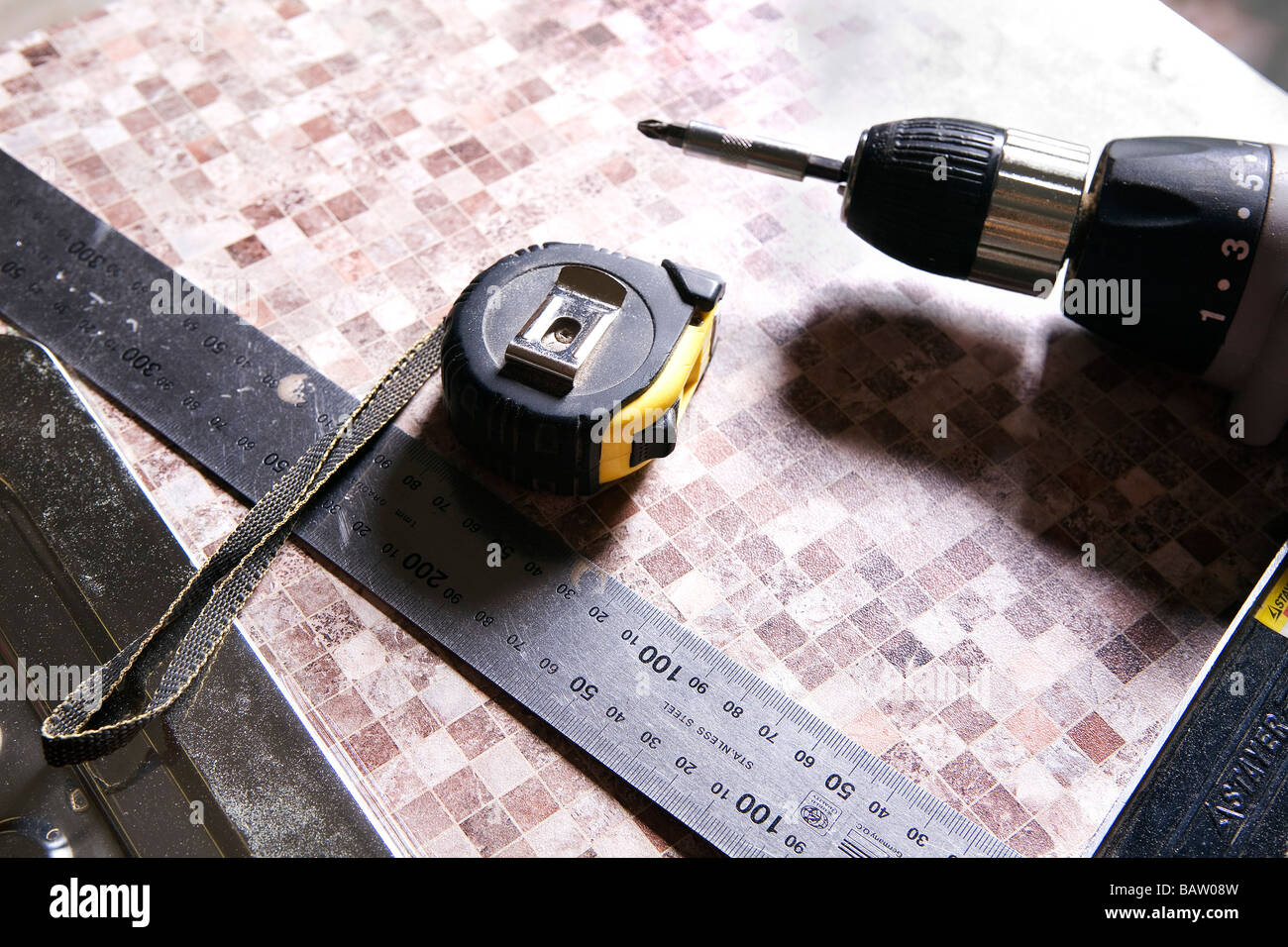 still life of ruler tape measure and cordless screwdriver - Stock Image