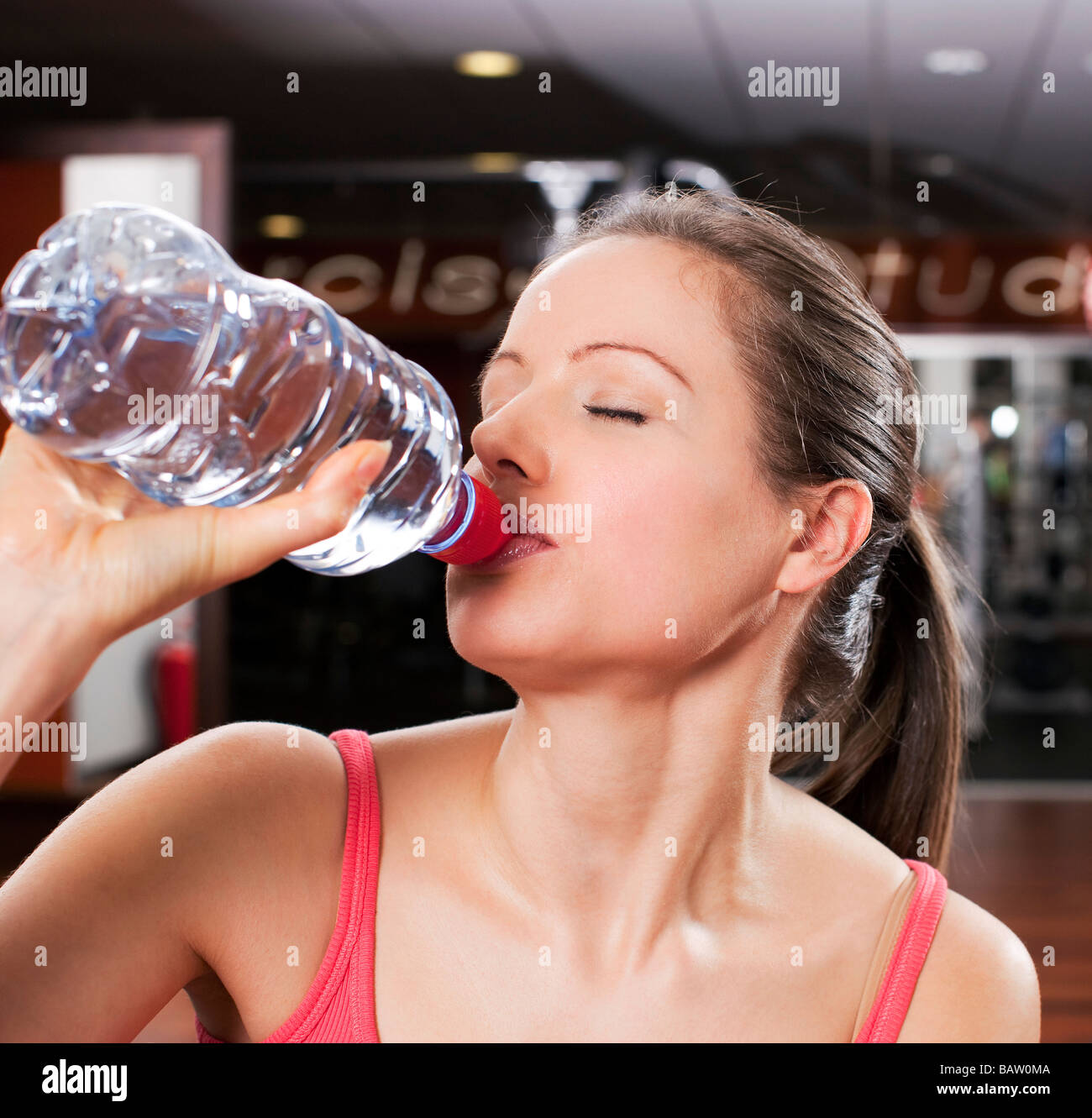 headshot of young drinking water from plastic bottle in gym - Stock Image
