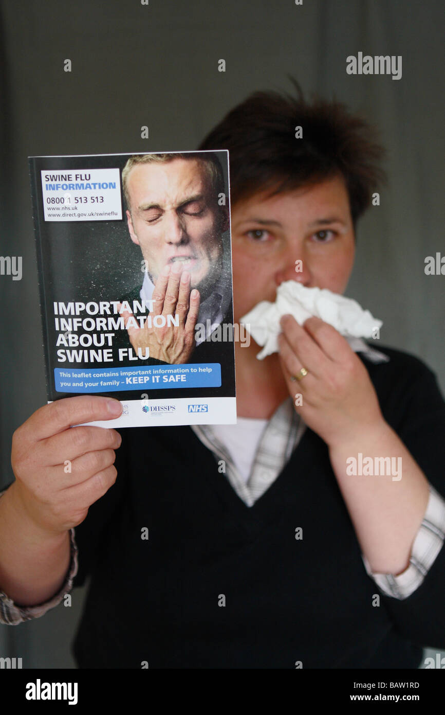 Swine Flu woman with paper tissues wiping nose holding the UK Government Swine Flu information leaflet booklet pamphlet - Stock Image