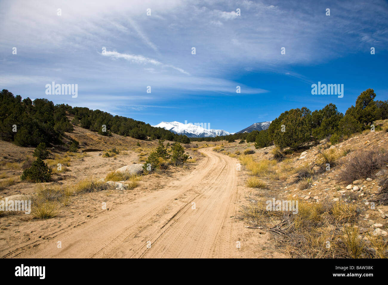 Dirt road in Chaffee County Colorado with the Collegiate Peaks in the distance - Stock Image