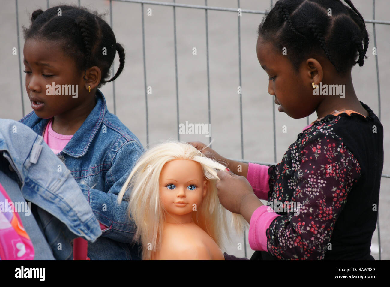 1c6776f226bce3 Young black girl child kid playing with blue eyes blonde plastic doll torso  combing hair outdoors 4s 5s 6s
