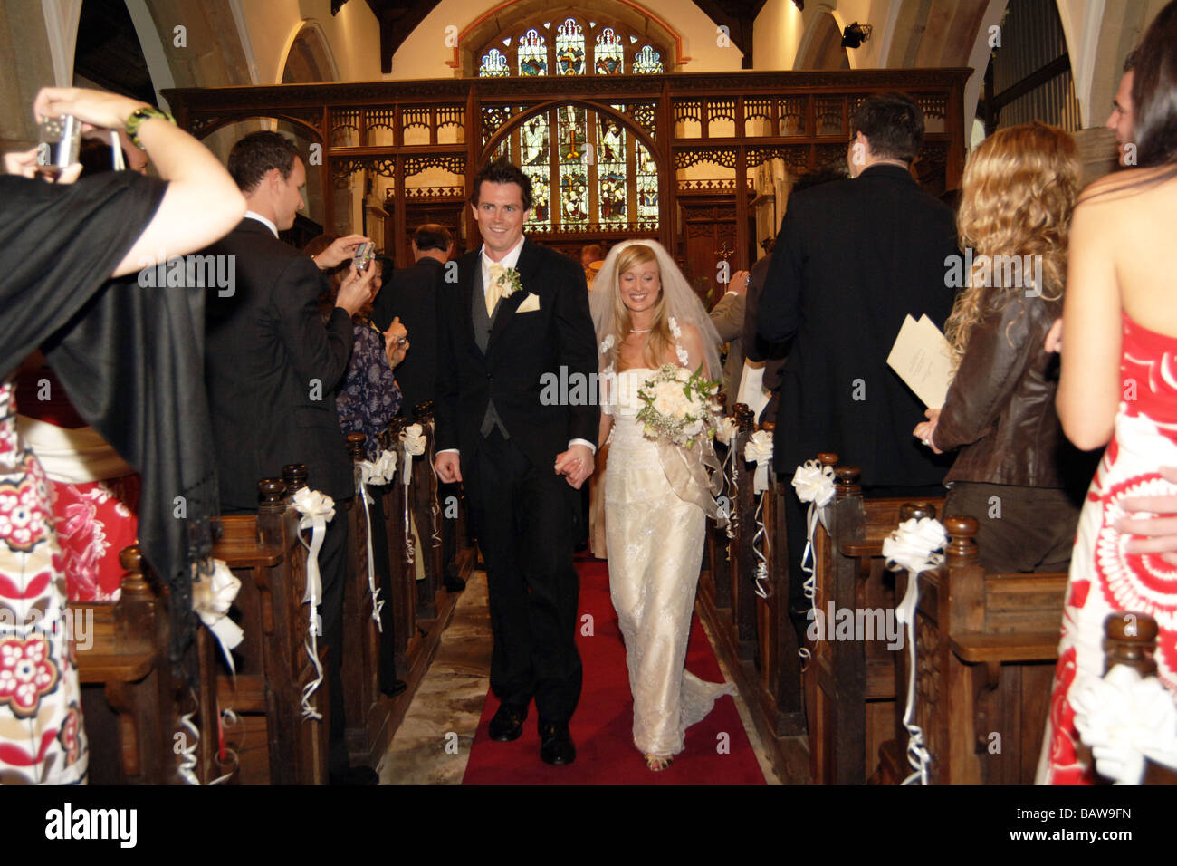 Young couple of newly weds walk down the church aisle North Yorkshire. UK MODEL RELEASED - Stock Image