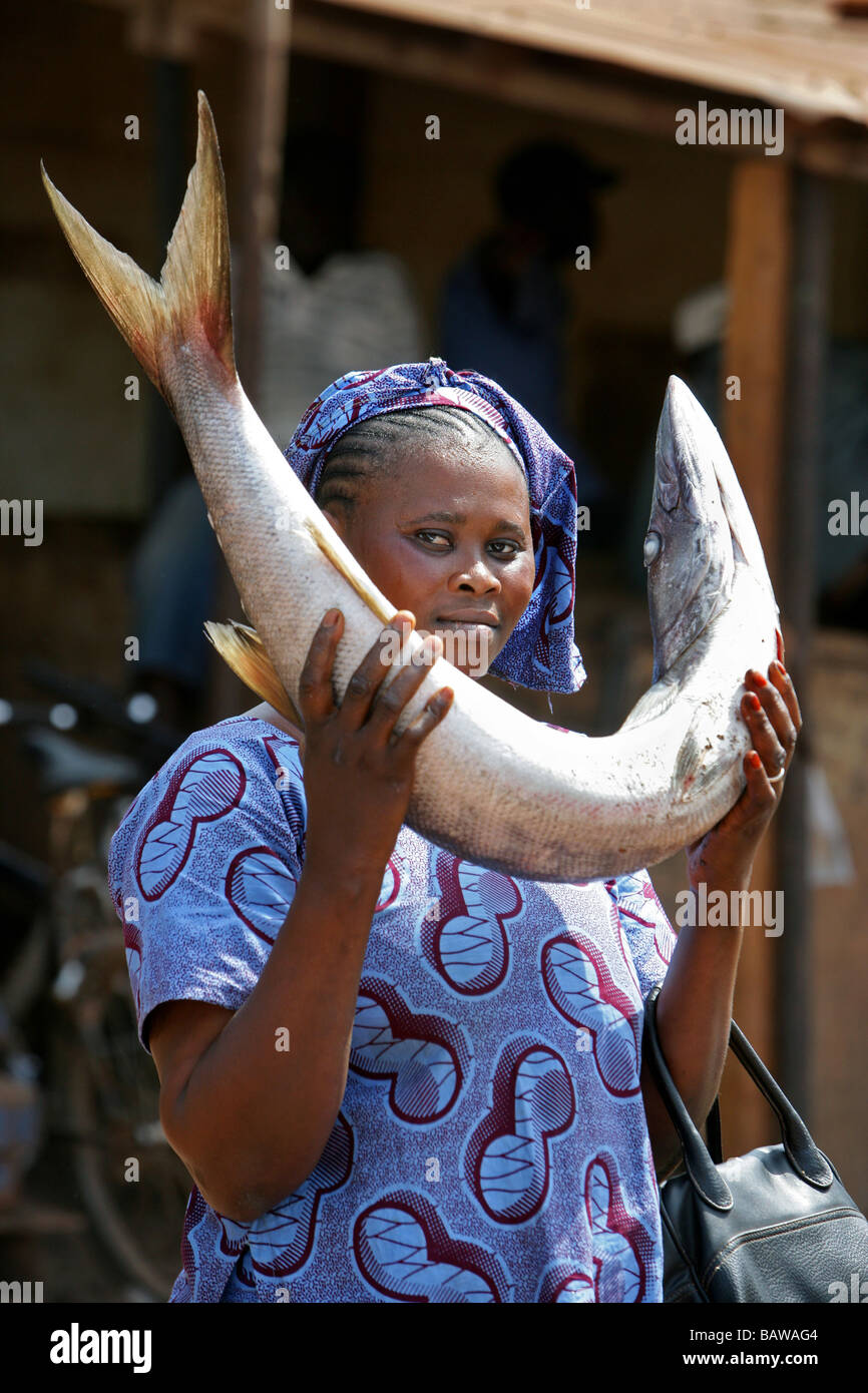 woman with baracuda fish at the fish marked in Kamsar, Guinea, West Africa - Stock Image