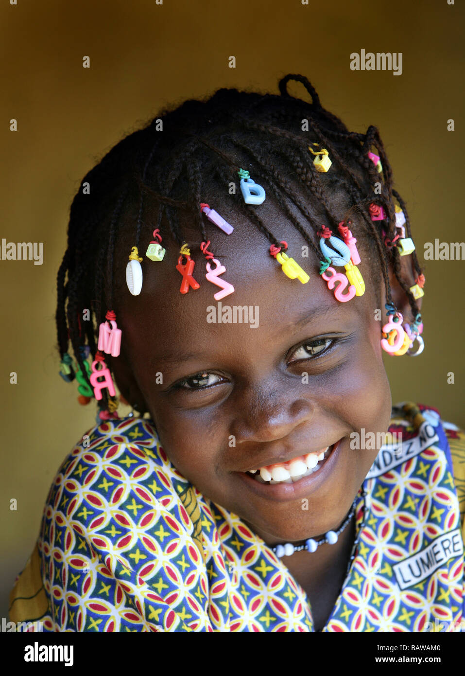 smiling girl with letters in her dreadlocks, Guinea, West Africa - Stock Image