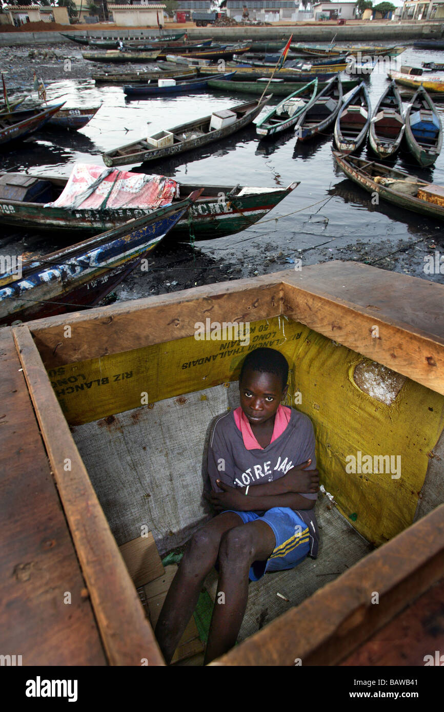 Guinea, Conakry: streetkid in his sleepingplace in a wooden box at the fishingport of Conakry - Stock Image