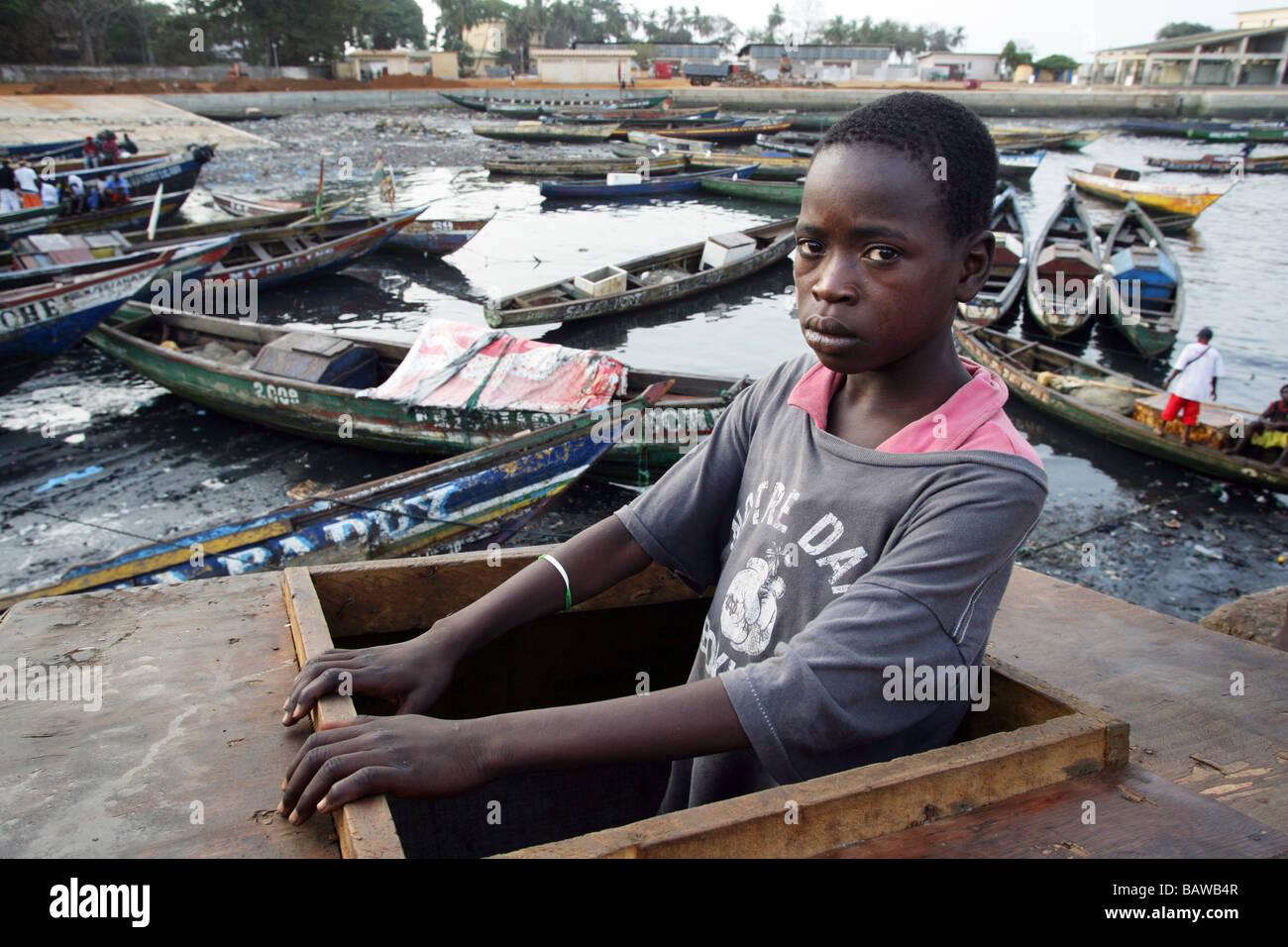 Guinea, Conakry: streetkid in his sleepingplace in a wooden box at the fishingport of Conacry - Stock Image