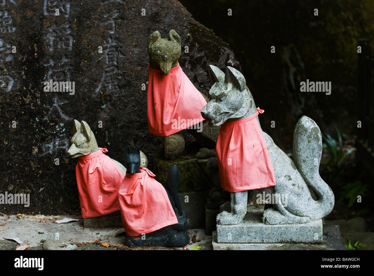 Inari fox statues in red bibs at the small Shinto Inari